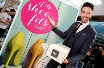 The picture shows a smiling presenter holding a box of shoes, he is standing on front of a promotional poster advertising the fun fashion game, If The Shoe Fits