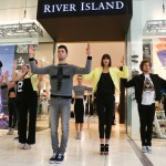 The picture shows a group of models/dancers performing a pop up fashion show directly outside a retails store in a shopping mall.