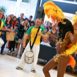 The picture shows a dancer in colourful carnival costume dancing to a Samba beat provided by a band of drummers. The smiling crowd in the background are enjoying the show.
