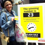 The pictures shows a smiling female student holding the prize winning ticket number, she is standing next to the in-store display of the matching number displayed in store