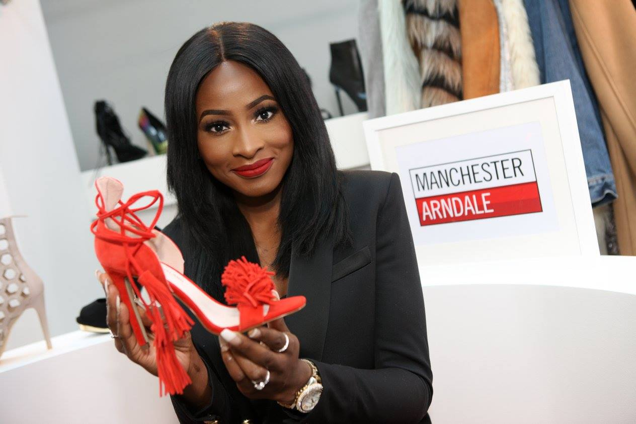 Woman holds up a shoe she likes at a retail event