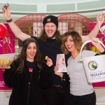 Group of three charity workers celebrate big donations to Cancer Research Wales by holding up collection buckets and cheering. They are stood in front of the giant Valentine heart installation at the Love Lock-In retail event Cardiff