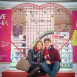 Couple sitting below giant Valentine heart installation filled with padlocks at Love Lock-In retail event, Cardiff