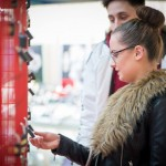 Woman looking at padlocks attached to giant Valentine heart installation at Love Lock-In retail event, Cardiff