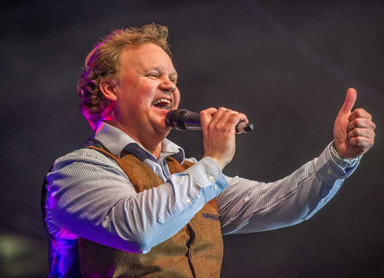 Close up portrait of smiling man holding microphone, addressing an audience, giving the thumbs-up sign. The man is children's TV presenter, Justin Fletcher AKA Mr Tumble
