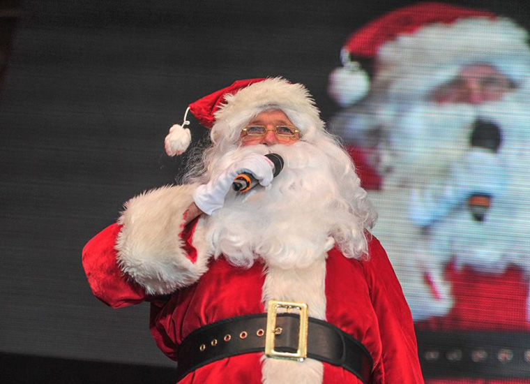 Close up portrait of a smiling man, dressed as Santa Claus, holding a microphone to address an audience.