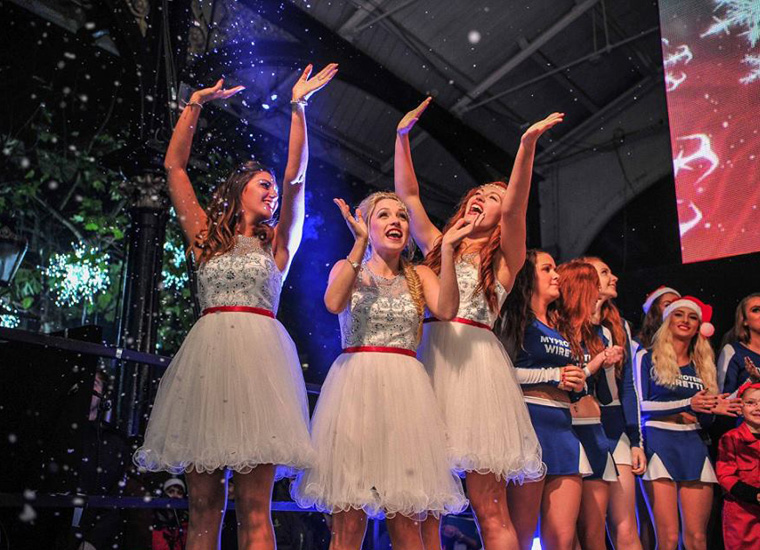Three smiling women stood on-stage hold their arms in the air as fake snow falls from the rooftop. In the background there are more women, some wearing Christmas hats