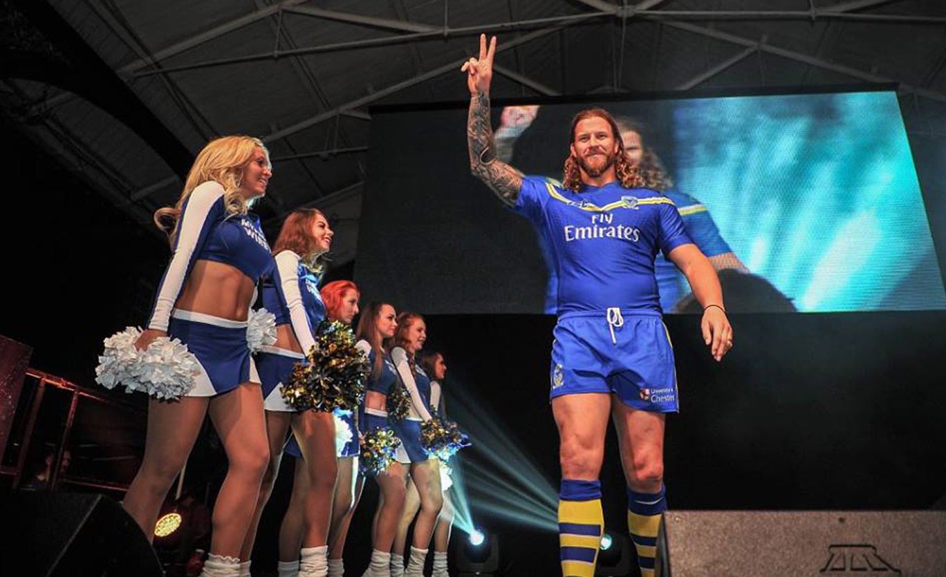 A group of female cheerleaders welcome onstage players from a rugby team. The team captain give the peace sign towards camera.