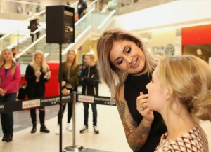 Makeup artist applying makeup to young woman's face during live beauty demonstration at shopping mall. In the background there are spectators.