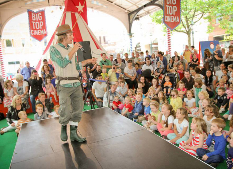 A large crowd of small children is gathered around a stage to watch a man holding a microphone perform in a summer event . The man is children's TV presenter, Ben Faulks AKA Mr. Bloom