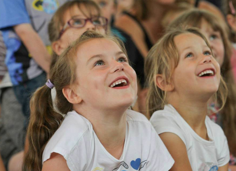 Close up portrait of smiling children reacting to an on-stage performance taking place off-camera.
