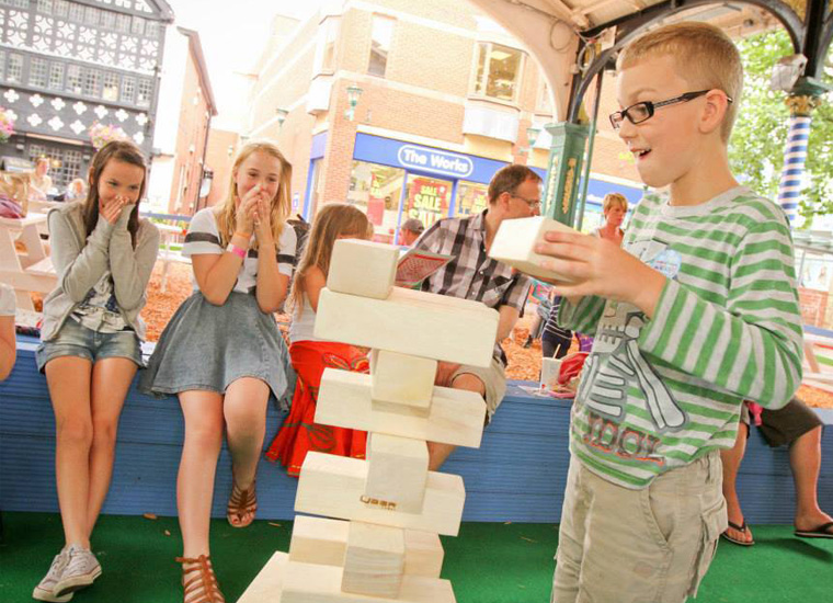 Two young girls watch and react to a little boy play a giant version of the game, Jenga. He tries to place a wooden block on top of an existing tower without it toppling over. The girls cover their faces in anticipation of the the tower falling.