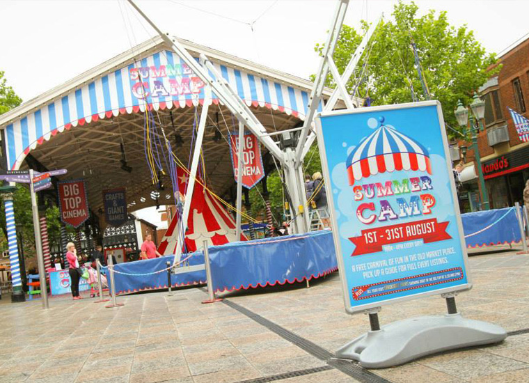 Free standing sign in outdoor shopping space advertises children's summer camp event. The covered event area is visible in the background and decorated in a fairground carnival style. There is a bungee fairground ride, lots of flags and giant teepee