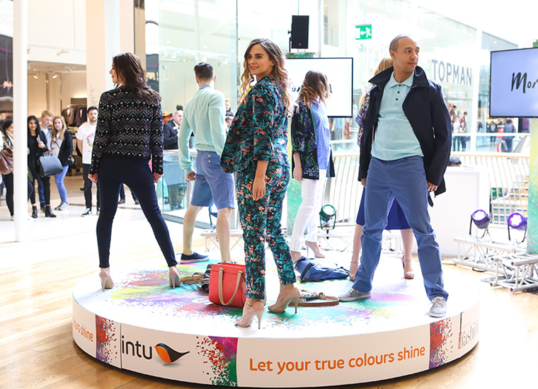 Four female and two male models pose on a circular catwalk in a busy shopping centre.