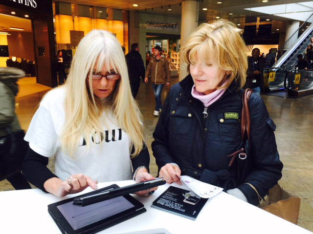 Two women, one customer and one brand associate are browsing iPads at an event in a shopping mall.