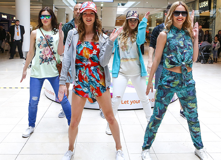 Four female and one male model pose facing camera in a busy shopping centre.