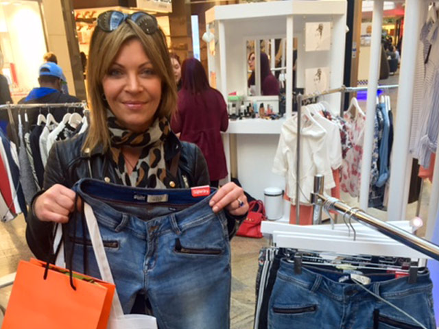 A stylish woman, standing next to clothing rails, holds a pair of jeans up towards camera at a shopping event