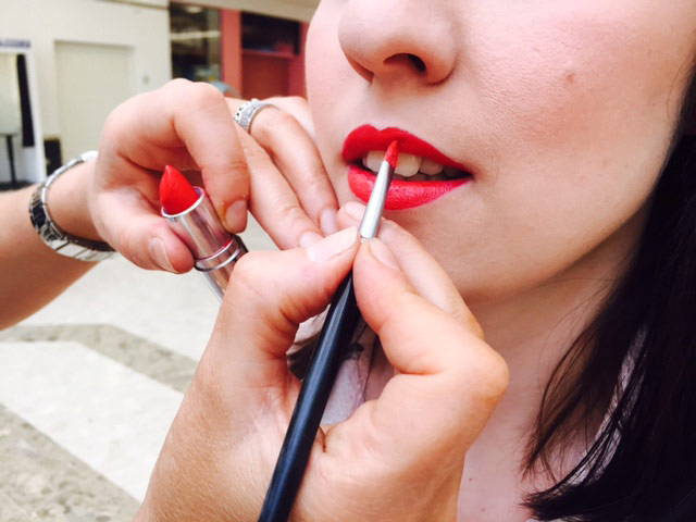 Close up detail of makeup artist's hands applying brightly coloured lipstick to young woman's lips