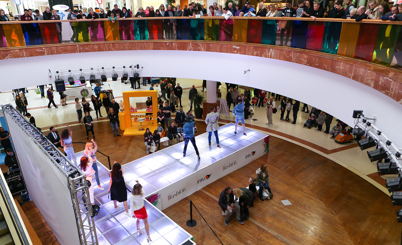 Crowds gather in a shopping centre to watch a catwalk fashion show. The image is seen from above, looking down on the models but two floors of the shopping centre are visible and there lots spectators upstairs and down.