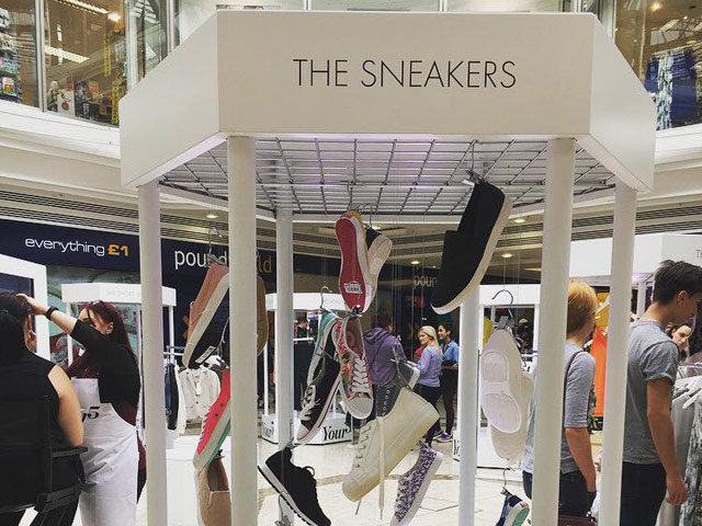 Detail of footwear display shows shoes hanging from invisible wires, they appear as if they are floating in space.