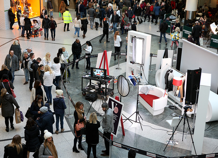 Pop up video production studio set up on shopping mall. Image shows crowds gathered around the set which has a camera and lighting, editing equipment, a sofa, clothing rails and product display units.