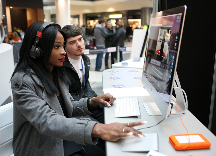 A young woman wearing headphones sits in front of a computer screen. She is assisted by a video production technician to edit her blog live on the mall of a busy shopping centre.
