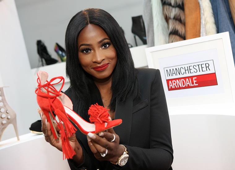 Smiling young woman presents a red shoe to camera.