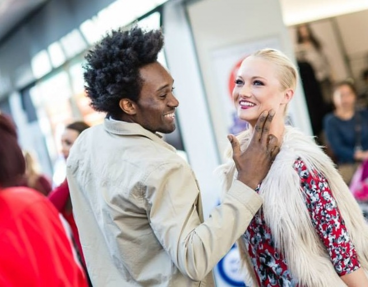 Male model tenderly touches the face of female model, both are smiling and dressed in stylish clothing.