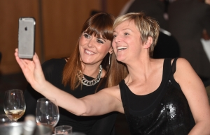 Two well dressed women are sat at a table during an evening awards ceremony, they are smiling into their smartphone taking selfies.