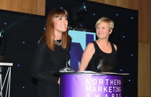 Smartly dresssed woman stood at podium, talking into microphone, making acceptance speech at Northern Marketing Awards. A second woman is standing off to the right, looking at the speaker and smiling.