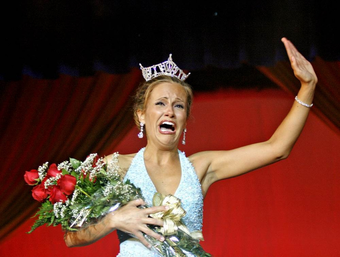 Portrait of female beauty pageant winner accepting her award. She is waving and crying with happiness, clutching a bouquet of roses and wearing a diamond tiara.