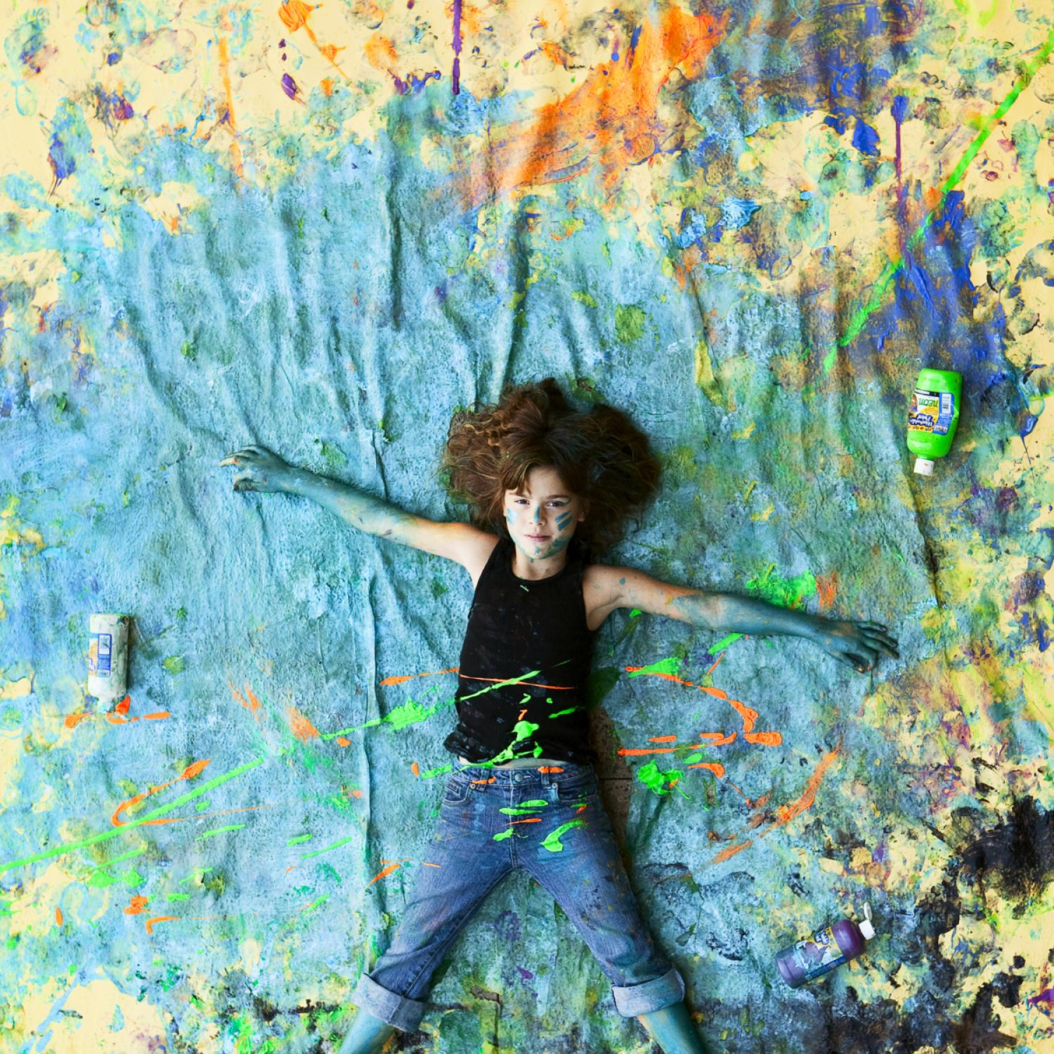 Experiential learning. Photo , shot from above, shows little girl lying on a paint splattered canvas. She is covered in paint and is loking up towards camera, smiling.