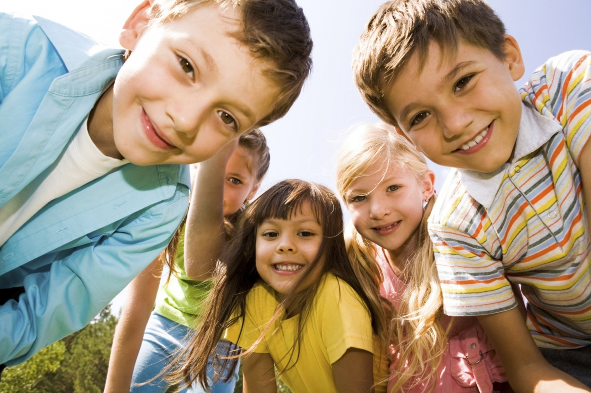 Close up photo of a group of friends, kids age 6-10, looking towards camera and smiling.