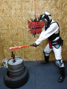 Retail-tainment - A man, wearing protective clothing, enjoys smashing objects with a baseball bat in the 'Wreck Room' experience at the outlets, Lake Elsinore in California, USA.