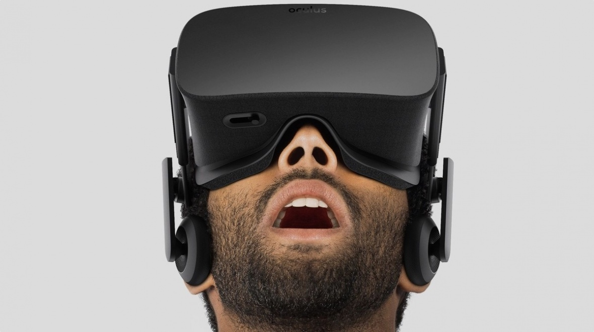 A man, wearing Virtual Reality googles, is looking upwards. His mouth is open in an expression of complete wonder.